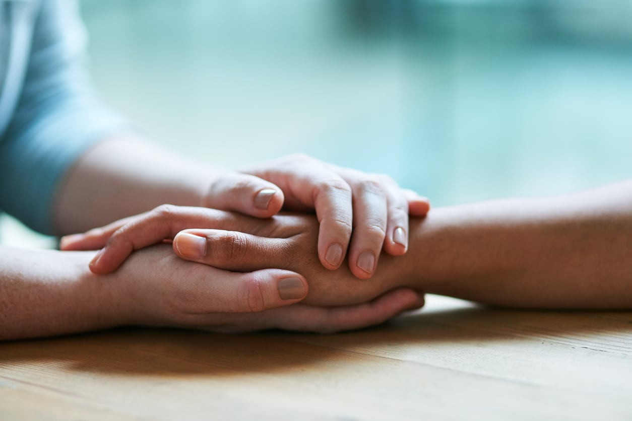 Shot of two people holding hands in comfort